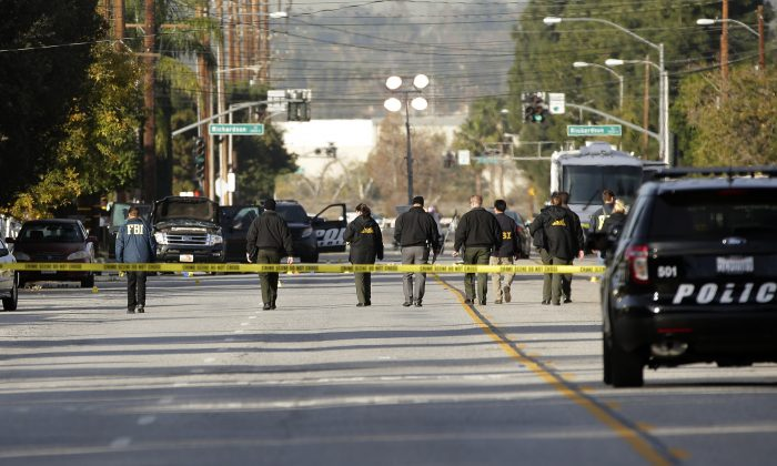 Investigators search for bullet casings at the scene where Wednesday's police shootout with suspects took place, in San Bernardino, Calif., on Dec. 3, 2015. (AP Photo/Jae C. Hong)