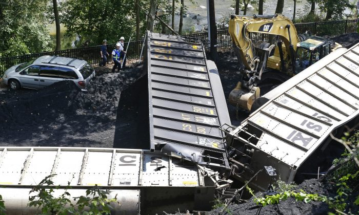 Officials (top L) inspect part of a CSX freight train that derailed alongside a parking lot overnight in Ellicott City, Md., on Aug. 21, 2012. A little-known truth about North American railroads: No rules govern when rail becomes too worn down. Since 2000, U.S. officials blamed rail wear as the direct cause of 111 derailments causing $11 million in damage. (AP Photo/Patrick Semansky)