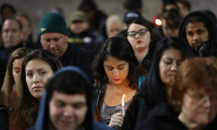 People hold candles on Dec. 3, 2015, as they attend a vigil at the San Manuel Stadium to remember those injured and killed during the shooting at the Inland Regional Center were killed in San Bernardino, Calif. (Joe Raedle/Getty Images)