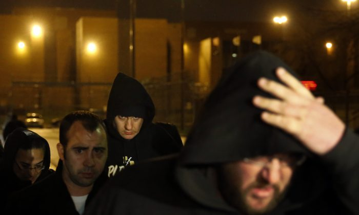 Chicago Police Officer Jason Van Dyke (background center) leaves the Cook County Jail after posting bond in Chicago on Nov. 30, 2015. Van Dyke has been locked up since Nov. 24, when prosecutors charged him with first-degree murder in the shooting death of black teenager Laquan McDonald. (AP Photo/Charles Rex Arbogast)