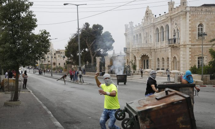 Palestinians clash with Israeli troops in front of the Intercontinental hotel in the West Bank city of Bethlehem on Oct. 23, 2015. (AP Photo/Nasser Shiyoukhi)