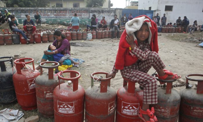 """Nepalese people sit near empty cooking gas cylinders lines as they wait for fresh supply in Kathmandu, Nepal, Monday, Nov. 16, 2015. Nepal's Prime Minister Khadga Prasad has asked neighboring India to lift an """"undeclared blockade,"""" saying the Himalayan nation is facing a severe fuel shortage and trouble obtaining medicine and food supplies blocked at the border. (AP Photo/Niranjan Shrestha)"""
