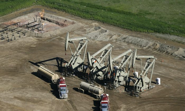 A pair of tanker trucks parked next to pumps at an oil-producing well in McKenzie County, N.D., on June 12, 2014. Lower fossil fuel prices have come at a painful cost: 122,300 lost jobs in the energy sector over the past year. Average wages have tumbled 1.5 percent to $26.72 an hour for energy production workers who kept their jobs, even as workers nationwide are earning slightly more money than a year ago. The November 2015 jobs report showed the sharp contrast between the overall economy and the ailing fossil fuels industry.(AP Photo/Charles Rex Arbogast)