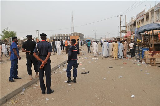 Security officers stand guard at the scene of an explosion at a mobile phone market in Kano, Nigeria. Wednesday Nov. 18, 2015 in this file photo. Boko Harem is also suspected in a December 5 attack on Lake Chad Island. (AP Photo/Muhammed Giginyu)