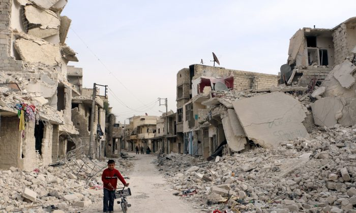 A Syrian boy walks with his bicycle in the devastated Sukari District in the northern Aleppo City on Nov. 13, 2014. (Baraa al-Halabi/AFP/Getty Images)