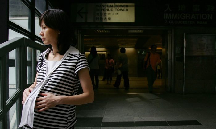 A pregnant woman stands in front of the entrance of Hong Kong Immigration Department on June 29, 2007, in Hong Kong, China. (M.N. Chan/Getty Images)