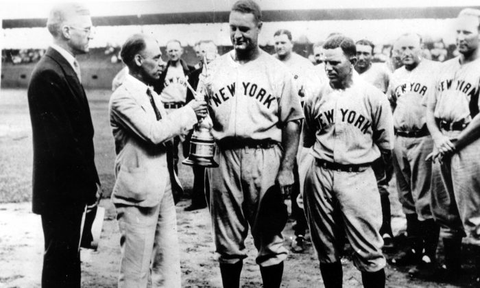 Lou Gehrig, first baseman for the New York Yankees, received a trophy in St. Louis, Aug. 17, 1933 when he played his 1,308th consecutive major league game. Left to right: President William Harridge of the American League; Edgar G. Brands, St. Louis newspaperman; Gehrig; and Joe Sewell, teammate of the new record holder. (AP Photo)