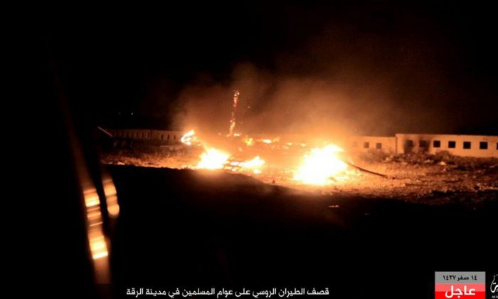 """Cars burning after Russian airstrikes that targeted civilian areas, in Raqqa, Syria, on Nov. 27, 2015. A new wave of airstrikes targeting the Syrian city of Raqqa, the headquarters of the extremist Islamic State and the focus of an international military campaign, killed several people, including children, Syrian opposition groups said Friday. The Arabic caption on the bottom picture reads:""""Russian airstrikes on the Muslims in Raqqa City."""" (Militant Amaq news agency via AP)"""