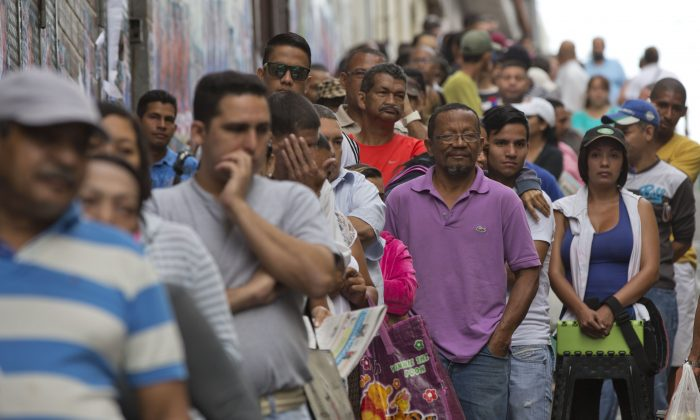 Voters wait in line at a polling station during congressional elections in Caracas, Venezuela, Sunday, Dec. 6, 2015. (AP Photo/Ariana Cubillos)