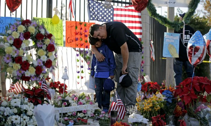 Gary  Mendoza, and his son Michael pay their respects at a makeshift memorial site honoring Wednesday's shooting victims in San Bernardino, Calif., on Dec. 7, 2015. (AP Photo/Jae C. Hong)