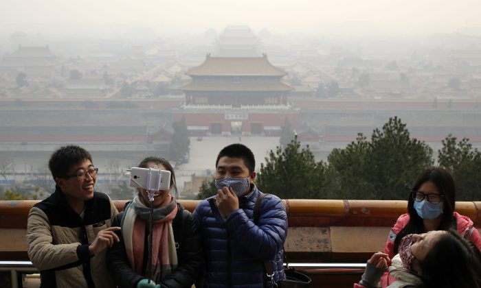 Visitors, some wearing masks to protect themselves from pollutants, share a light moment as they take a selfie at the Jingshan Park on a polluted day in Beijing on Dec. 7, 2015. (AP Photo/Andy Wong)