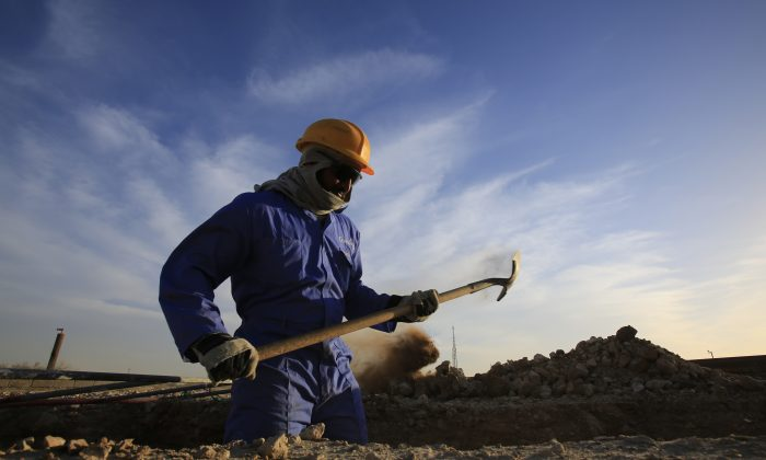 An oil worker shovels at a facility site in the desert oil fields of Sakhir, Bahrain, Monday, Dec. 7, 2015. U.S. stocks are dropping in early trading Monday as investors dump energy companies on lower oil prices. Benchmark U.S. crude is trading near its closing low for the year following a decision by OPEC last week not to cut production. (AP Photo/Hasan Jamali)