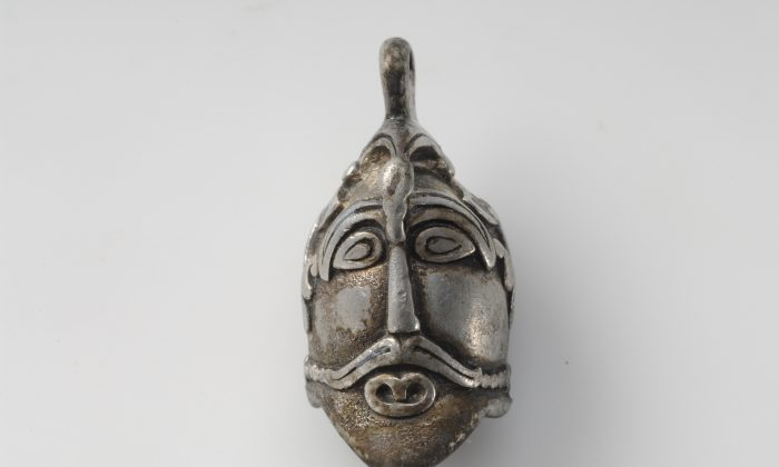 This silver pendant in the shape of a man's head comes from a unique grave find containing objects of precious metals that mark the deceased as someone of great importance. Close inspection reveals he wears a bird atop his head with its wings extending down to his ears.  (© The Swedish History Museum)