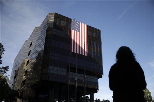 Emily Petrus, a worker for San Bernardino County, pauses to look at a large flag hanging on San Bernardino City Hall on Monday, Dec. 7, 2015 in San Bernardino, Calif. County employee's returned to work today after Wednesday's mass shooting. Thousands of employees of San Bernardino County are preparing to return to work Monday, five days after a county restaurant inspector and his wife opened fire on a gathering of his co-workers, killing 14 people and wounding 21.  (AP Photo/Jae C. Hong)