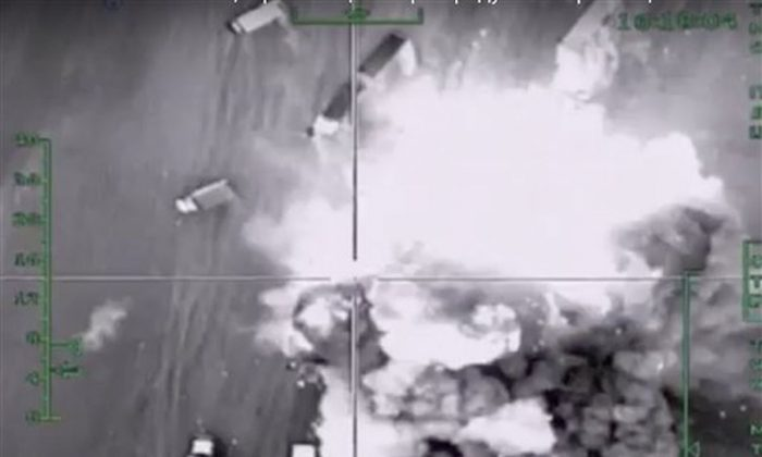 In this photo made from the footage taken from Russian Defense Ministry official web site on  Friday, Dec. 4, 2015 an aerial image of what they purport shows an airstrike on an automobile column transporting oil products in Aleppo province, Syria. (AP Photo/Russian Defense Ministry Press Service)