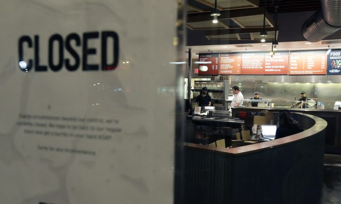 "People stand inside a closed Chipotle restaurant on Monday, Dec. 7, 2015, in the Cleveland Circle neighborhood of Boston. Chipotle said late Monday that it closed the restaurant after several students at Boston College, including members of the men's basketball team, reported ""gastrointestinal symptoms"" after eating at the chain. The school said it was working with local health officials to determine the cause of the illness. (AP Photo/Steven Senne)"