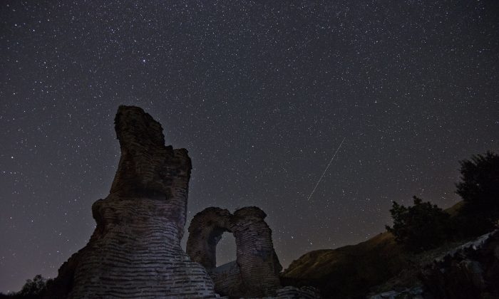 A Perseids meteor (R) streaks across the night sky over the remains of St. Ilia Roman near the town of Pirdop on Aug. 12. (NIKOLAY DOYCHINOV/AFP/Getty Images)