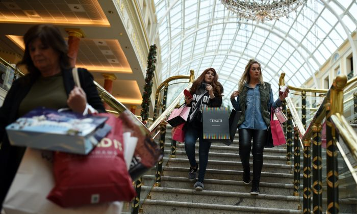 Shoppers walk through the Trafford Centre shopping mall past retailers offering 'Black Friday' discounts in Manchester, northern England on November 27, 2015 (Oli Scarff/AFP/Getty Images)