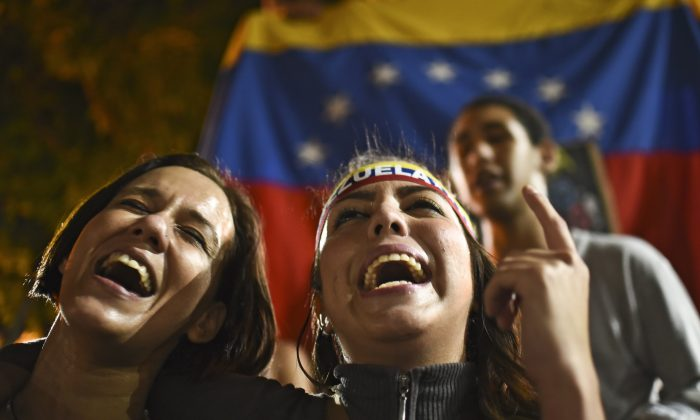 Venezuelan opposition supporters celebrate the results of the legislative election in Caracas on Dec. 7, 2015. Venezuela's jubilant opposition vowed Monday to drag the oil-rich country out of its economic crisis and free political prisoners after winning control of congress from socialist President Nicolas Maduro. (Luis Robayo/AFP/Getty Images)