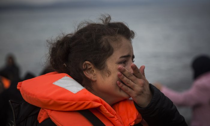 A girl cries on a beach on the northeastern Greek island of Lesbos, after crossing the Aegean sea on a dinghy with other refugees and migrants from the Turkey's coast, on Tuesday, Nov. 24, 2015. (AP Photo/Santi Palacios)