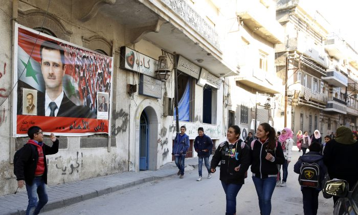 """School students walk past a big poster of Syrian President Bashar Assad in the old city of Homs on Tuesday, Dec. 8, 2015. Once Syrian opposition fighters start pulling out of the last rebel-held area of Homs this week, the city once known as the """"capital of the revolution"""" will return fully to government control. But its inhabitants have only been trickling back and many neighborhoods are still ravaged and deserted _ a sign of the enormous challenges the government faces in reasserting its authority over areas once held by the opposition. (AP Photo)"""