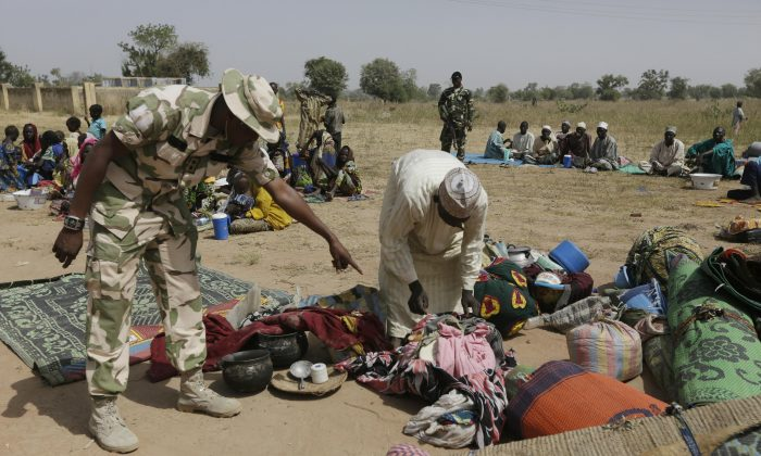 Soldiers screen newly arrived displaced people at Furore camp in Yola, Nigeria, on Tuesday, Dec. 8, 2015, who claim were chased out of their villages by Cameroon troops. Cameroonian troops crossed the border into Nigeria, killing and pillaging and ordering people to abandon their villages, according to hundreds of survivors arriving at a refugee transit center after walking for days. (AP Photo/Sunday Alamba)