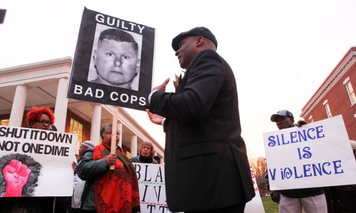 La Mar T. Gunn, center, president of the Central Delaware NAACP, addresses the protestors gathering outside as the sun sets on the Kent County Courthouse after the announcement that jury deliberations will continue tomorrow. Jurors ended a second day of deliberations with no verdict Monday, Dec. 7, 2015, in the trial of a white Delaware police officer charged with assault after breaking a black suspect's jaw with a kick. (Suchat Pederson/The Wilmington News-Journal via AP)