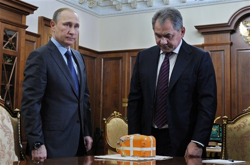 Russian Defense Minister Sergei Shoigu, right, shows President Vladimir Putin a flight recorder of a Russian warplane shot down by a Turkish jet on Nov. 24, in the Novo-Ogaryovo residence outside Moscow, Russia, Tuesday, Dec. 8, 2015.  Shoigu said Syrian and Russian troops had recovered the plane's flight recorder and Putin ordered it to be studied in the presence of foreign experts. (Mikhail Klimentyev/Sputnik, Kremlin Pool Photo via AP)