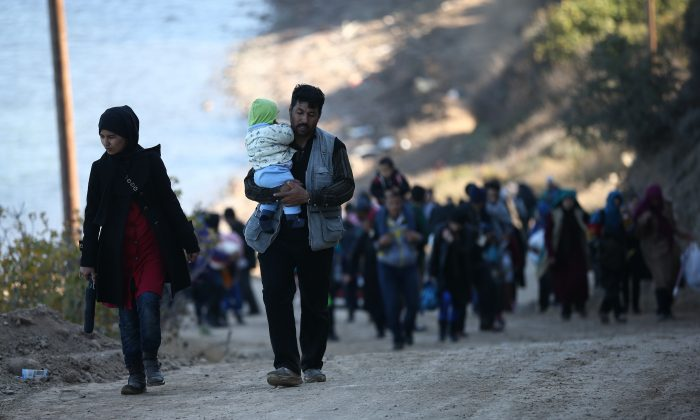 Migrants walk to a reception center after making the crossing from Turkey to the Greek island of Lesbos, in Sikaminias, Greece, on Nov. 13, 2015. (Carl Court/Getty Images)
