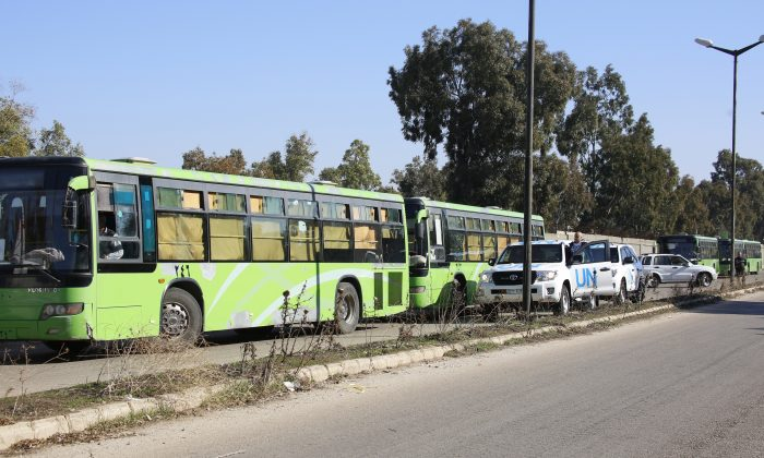 Buses carrying gunmen leave the Waer neighborhood, in the central city of Homs, Syria, Wednesday, Dec. 9, 2015. (AP Photo)