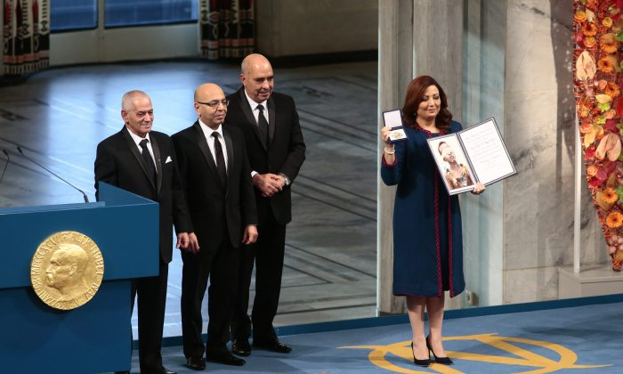 The winners of the 2015 Nobel Prize, Tunisian National Dialouge Quartet members,  from left to right,  Houcine Abassi, Mohamed Fadhel Mahfoudh, Abdessattar Ben Moussa and Wided Bouchamaoui, holding the award at the Nobel Peace Prize award ceremony in Oslo, Norway, Wednesday Dec.10. 2015. (Haakon Mosvold Larsen / NTB scanpix via AP)