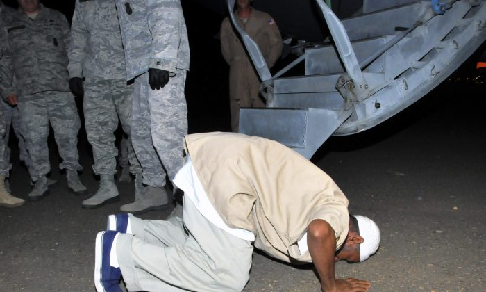 Sudanese national, Ibrahim al-Qosi, in his 50s, a former al-Qaida cook released from Guantanamo, prays upon arrival at Khartoum airport in Khartoum, Sudan, Wednesday, July 11, 2012. Al-Qosi arrived before dawn on a US Air Force aircraft after his release from 10 years in detention. (AP Photo/Abd Raouf)