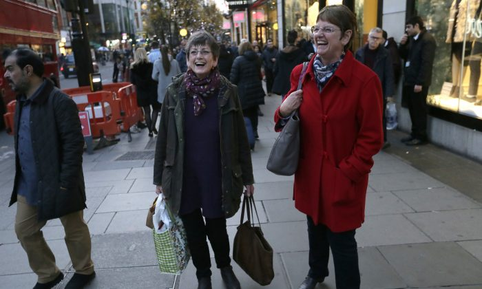 Hazel Newton, centre left, poses for a picture with her sister as they walk down Oxford Street, in London, Wednesday, Dec. 9, 2015. (AP Photo/Tim Ireland)