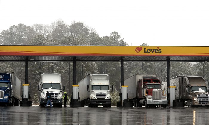 FILE - In this Feb. 11, 2014, file photo, truck drivers stop at a gas station in Emerson, Ga., north of metro Atlanta, to fill up their tractor trailer rigs.  (AP Photo/David Tulis, File)