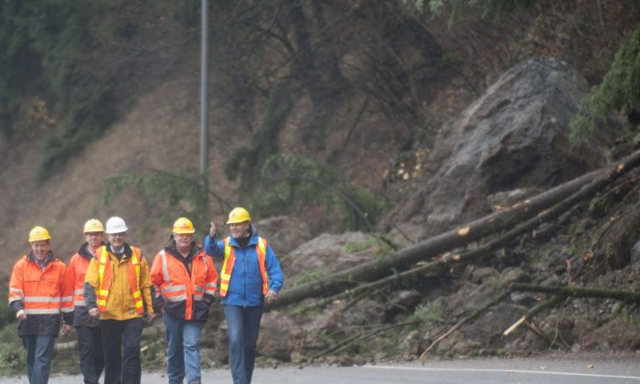 Washington Gov. Jay Inslee, right,  is briefed by department of transportation officials as they survey the scene of a mudslide obstructing the northbound lane of Interstate 5 near Woodland,, Was., Thursday, Dec. 10, 2015. Boulders, trees and dirt slid onto the highway in the day before following heavy rains. (Natalie Behring/The Columbian via AP) MANDATORY CREDIT