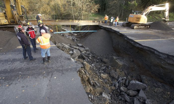 Fire and maintenance personnel look at a large sinkhole on Kane Drive in Gresham, Ore., Wednesday, Dec. 9, 2015. Torrential rains pummeled parts of the Pacific Northwest early Wednesday, causing mudslides and flooding roads. (AP Photo/Steve Dipaola)
