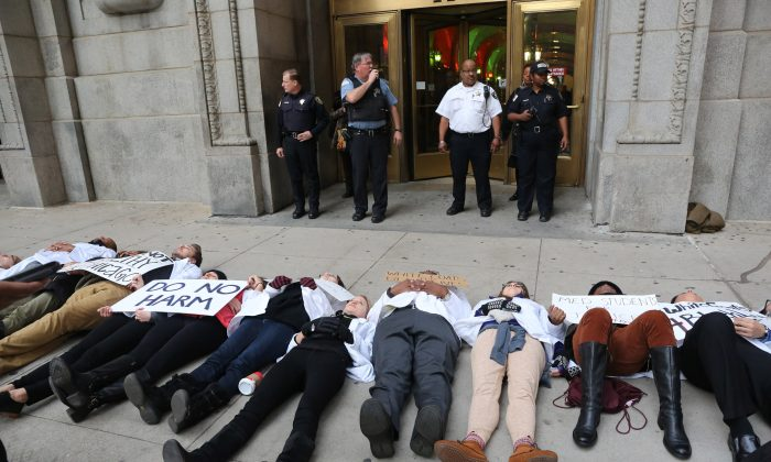 """Dozens of medical students from various Chicago student associations stage a """"die in"""" outside the county building, Thursday, Dec. 10, 2015, to protest the killing of Laquan McDonald by a police officer in Chicago. Many activists and analysts say the steps Mayor Rahm Emanuel is taking to hold Chicago police officers accountable for abuses are way too timid. It's tinkering at the edges of deeply flawed structures or merely switching around managers, they argue, when what's needed is to scrap the entire system and start all over.(Antonio Perez/Chicago Tribune)"""