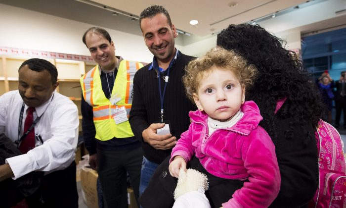 Madeleine Jamkossian, right, arrives with her family, refugees fleeing from Syria, at Pearson International airport, in Toronto, on Dec. 11, 2015. (Nathan Denette/The Canadian Press via AP)