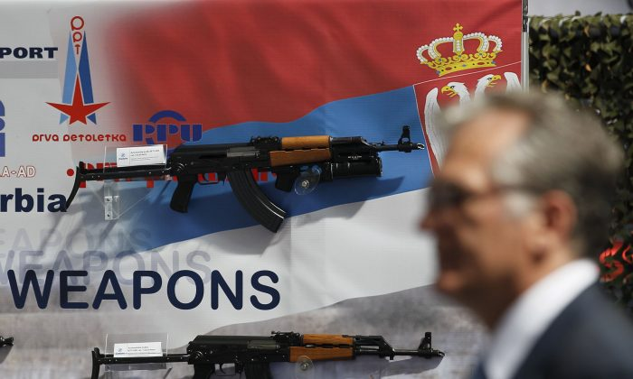 In this Tuesday June 28, 2011 file photo, a visitor looks at assault rifles made by the Serbian company Zastava Arms, during a defense fair, in Belgrade, Serbia. The head of a Serbian arms factory, Milojko Brzakovic, director of the Zastava factory, says several weapons used by Islamic militants during the Paris attacks have been identified as produced by his company in the early 1990s. (AP Photo/Darko Vojinovic, File)