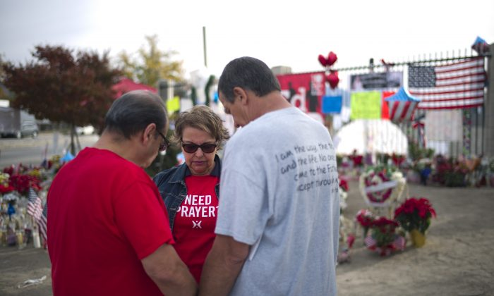 Ray Molina, from left, Molina's wife, Yvonne, and Leonard Lynch pray at a makeshift memorial set up near the Inland Regional Center, the site of last week's fatal shooting that killed 14 people, Wednesday, Dec. 9, 2015, in San Bernardino, Calif. The two San Bernardino shooters were radicalized at least two years ago, a year before one of them came to the U.S. on a fiancée visa, and discussed jihad and martyrdom as early as 2013, FBI Director James Comey said Wednesday. (AP Photo/Jae C. Hong)