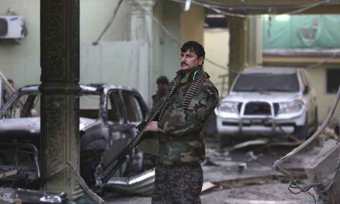 An Afghan security forces member stands guard at the Spanish Embassy after an attack in Kabul, Afghanistan, Saturday, Dec. 12, 2015. (AP Photo/Rahmat Gul)