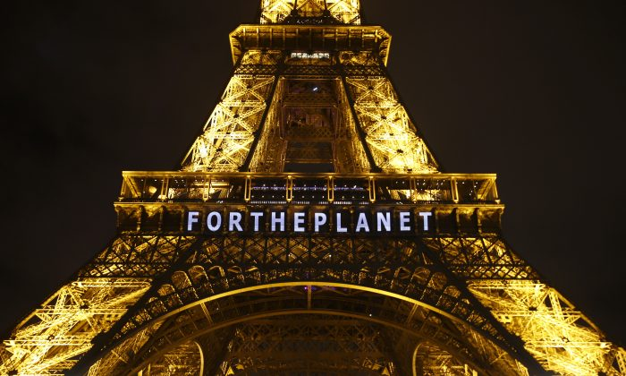 "The slogan ""FOR THE PLANET"" is projected on the Eiffel Tower as part of the COP21, U.N. Climate Change Conference in Paris, France, on Friday, Dec. 11, 2015. (AP Photo/Francois Mori)"