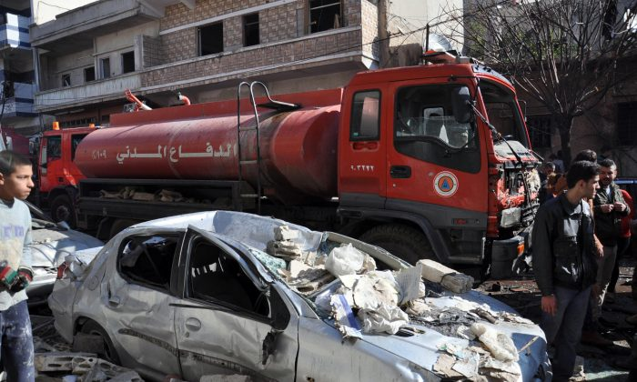 A firefighter truck is seen next to a destroyed car at the site of a car bomb explosion where 16 civilians were killed and a hundred wounded in al-Zahra neighborhood in Homs, Syria, on Dec. 12, 2015. (STR/AFP/Getty Images)