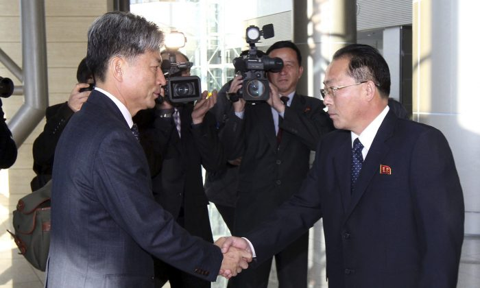 Hwang Boogi (L), South Korea's vice minister of unification and the head negotiator for high-level talks with North Korea, shakes hands with his North Korean counterpart Jon Jong Su (R), before their meeting at the Kaesong Industrial Complex in Kaesong, North Korea, Friday, Dec. 11, 2015. North and South Korea on Friday held high-level talks at a North Korean border town, a small step meant to improve ties battered by a military standoff in August and decades of acrimony and bloodshed. (Yonhap via AP)
