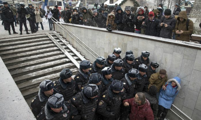 Police officers block the way to prevent people attending an opposition rally in Pushkin Square in Moscow, Russia, Saturday, Dec. 12, 2015. Police report that over a dozen participants in an opposition rally held in support of the Russian constitution were detained. The Day of the Constitution is marked on Dec. 12 in Russia. (AP Photo/Pavel Golovkin)