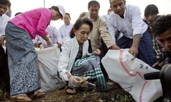 Leader of National League for Democracy party (NLD) Aung San Suu Kyi (front C) picks garbage during a clean-up drive initiated by Suu Kyi in Kawhmu, Burma, Sunday, Dec. 13, 2015. Suu Kyi lead the garbage collection on early foggy Sunday in Kawhmu township of Yangon region, where she won her seat for the Lower House in the country's general election. (AP Photo/Gemunu Amarasinghe)