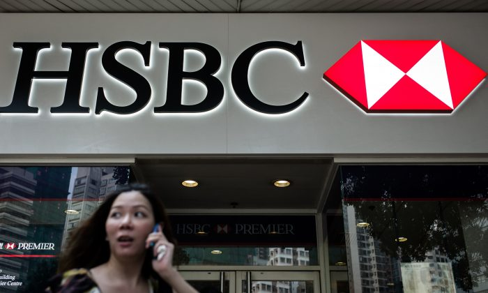 A woman stands outside of a HSBC branch in Hong Kong on July 8, 2014. (Philippe Lopez/AFP/Getty Images)
