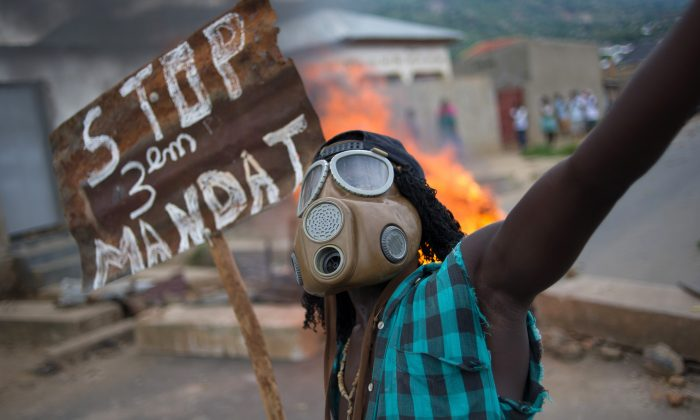 A Burundian protester wearing a gas mask holds a sign that reads 'Stop the third mandate' near a burning barricade in the Mugasa neighbourhood of Bujumbura on May 6, 2015. (Phil Moore/AFP/Getty Images)