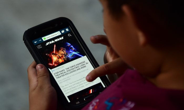 A child browses on a mobile phone Oct. 20 in Los Angeles. (Photo credit should read FREDERIC J. BROWN/AFP/Getty Images)