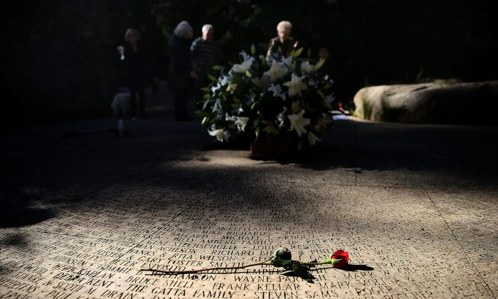 A flower lays on the engraved names of AIDS victims at the National AIDS Memorial Grove in San Francisco, Calif., on Dec. 1, 2015. World AIDS Day has been observed on Dec. 1 since 1988, and is dedicated to raising awareness of the AIDS pandemic caused by the spread of HIV infection, and to mourn those who have died from the disease. (Justin Sullivan/Getty Images)